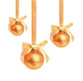 Hunging guld- julbollar som isoleras på en vit Royaltyfri Foto