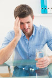 Hungover businessman holding glass of water and tablet Stock Photos