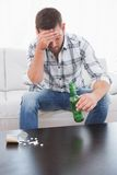 Hungover mężczyzna z piwem i jego medycyna kłaść out na stolik do kawy Obrazy Stock