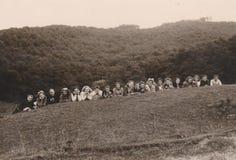 HUNGRÍA CIRCA las señoras jovenes 1930 del ` s con el franciscano en un campo del ` s del estudiante imagen de archivo libre de regalías