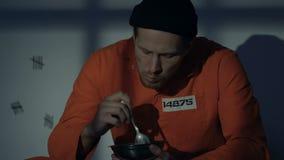 Hungrig Caucasian fånge som äter mål i cellen, fruktansvärd äcklig mat, villkor lager videofilmer