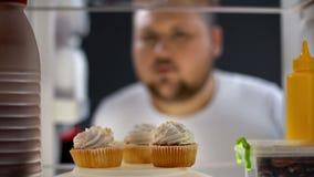 Hungrig fet man som ser kräm- kakor i kyl på natten, sockersjuka risk, socker arkivfoton