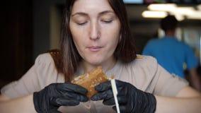 Hungrig flicka i svarta handskar som äter en saftig hamburgare i ett kafé arkivfilmer