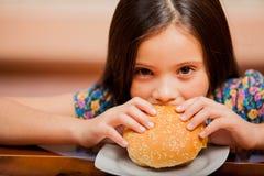 Hungrig flicka som äter en hamburgare arkivbild