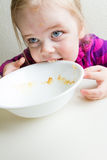 Hungrig flicka som inte ges nog mat. Arkivfoton
