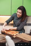 Hungrig flicka som sitter på kök som har matställen av italiensk pizza arkivbilder