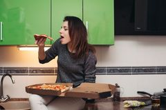 Hungrig flicka som sitter på kök och äter smaklig pizza royaltyfria bilder