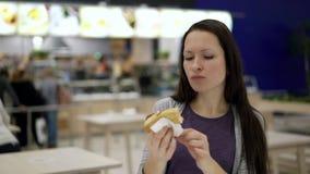 Hungrig kvinna som äter på matdomstolen i shoppinggalleria Ung nätt kvinna som tuggar den smakliga varmkorven på snabbmatrestaura stock video