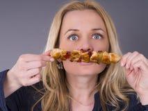 Hungrig kvinna som luktar grillat kött royaltyfria bilder