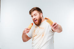 Hungrig man i den smutsiga skjortan som går att äta två hotdogs Arkivfoto