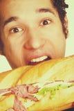 Hungrig man som äter smörgåsen arkivbilder
