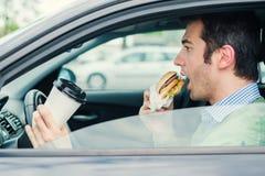 Hungrig man som kör hans bil, medan äta mat i trafiken arkivbilder