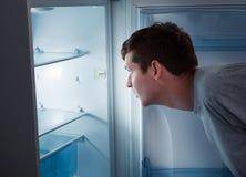Hungrig man som ser i kylskåp Arkivbild