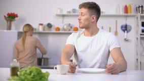 Hungrig man som väntar ivrigt på matställen, fru som lagar mat på bakgrund, svält arkivfilmer