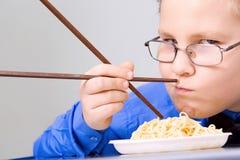 Hungrig pojke som äter kinesiska nudlar med sticks Arkivfoton