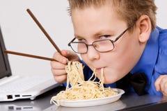 Hungrig pojke som äter kinesiska nudlar med sticks Royaltyfria Bilder