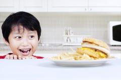 Hungrig pojke som ser nötkötthamburgaren Royaltyfri Bild