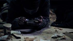 Hungrig tiggare som äter från stålbunken som sitter på den smutsiga lådan, gatauppehälle royaltyfri foto