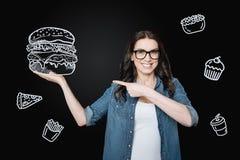 Hungrige Frau, die bei der Einrichtung eines riesigen Hamburgers aufgeregt glaubt Lizenzfreie Stockfotos