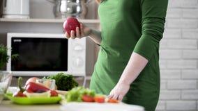 Hungrige Frau, die in der Hand roten Apfel für Snack, gesunde Wahl, Vitamine hält lizenzfreie stockfotografie