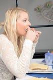 Hungrige Frau, die eine Rolle isst Stockfotografie