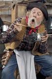 Hungriger alter Cowboy, der Bohnen von einer Kasserolle isst Lizenzfreie Stockfotografie