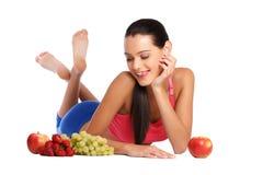 Hungriger Brunettejugendlicher mit gesunden Früchten Stockfotos