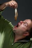 Hungriger corpulent Mann, der entlang eines Fisches anstarrt lizenzfreie stockbilder