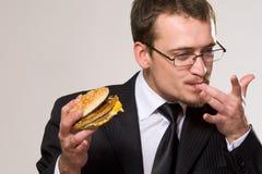 Hungriger Geschäftsmann, der Hamburger isst Stockfoto