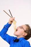 Hungriger Junge, der chinesische Nudeln mit Steuerknüppeln isst Lizenzfreie Stockbilder