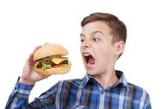 Hungriger Junge möchte einen großen Hamburger essen stockbild