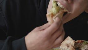Hungriger junger Mann, der unersättlich eine Pizza im Café isst stock video footage