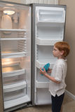 Hungriger kleiner Junge, der leeren Kühlschrank untersucht Stockbilder