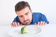 Hungriger Mann, der vor einem Teller mit einem Kohl traurig sich fühlt Lizenzfreies Stockfoto