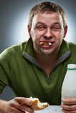 Hungriger Mann mit dem Mund voll vom Brot Stockfotografie