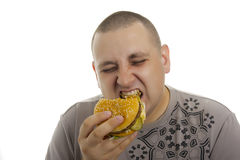 Hungriger Mann mit Hamburger. Lizenzfreie Stockfotografie