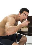 Hungriger muskulöser hemdloser Mann, der hinunter Lebensmittel schluckt lizenzfreie stockfotografie