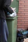 Hungriger obdachloser Mann, der nach Lebensmittel in einem Müllcontainer sucht Lizenzfreies Stockbild