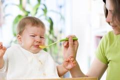 Hungriges Baby, das Lebensmittel nahe bei seiner Mutter isst. Stockfotos