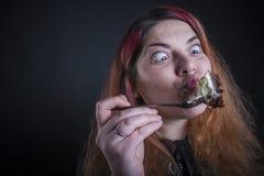 Hungriges beleibtes Mädchen, das über Kuchen starkes Verlangen hat Lizenzfreie Stockbilder