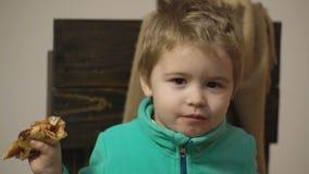 Hungriges Kind, das einen Biss von der Pizza nimmt Junge in einer gr?nen Strickjacke isst eine Pizza beim Sitzen auf einem Holzst stock footage