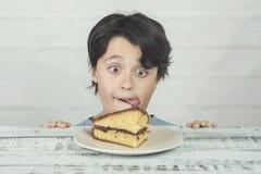 Hungriges Kind, das Stück des Kuchens isst lizenzfreie stockfotografie