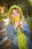 Hungriges Mädchen, das grünen Schal und den Hut draußen isst Apple trägt Stockfoto