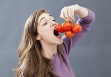 Hungriges schönes Mädchen, das herauf Tomaten mit Appetit und Habsucht isst lizenzfreie stockfotos