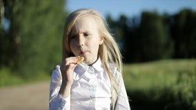 Hungriges Schulmädchen im weißen Hemd und im schwarzen Rock geht durch die sandige Straße durch das Feld und isst einen Keks stock video footage