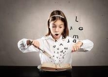 Hungrigt flickasammanträde på tabellen framme av en bok arkivbild