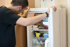 Hungry. A young hungry guy checking the fridge for something to eat royalty free stock photo