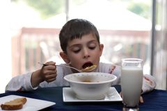 Hungry. 6 year old boy having breakfast in the morning royalty free stock photography