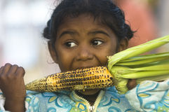 Hungry. Small Indian girl eating corn on the cob, beach near Chennai, Tamil Nadu, India Stock Photo