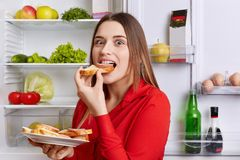 Hungry adorable woman eats delicious sandwhiches with cheese and sausage, stands near opened refrigerator full of products. Beauti. Ful female feels hunger after Royalty Free Stock Photography